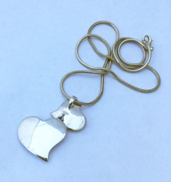 Zilveren ketting met een hanger van twee hartjes.