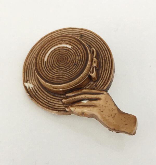 Broche met hand die een hoed vasthoudt