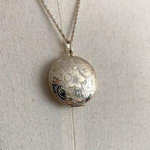 rond zilveren medaillon met geëtste bloemen